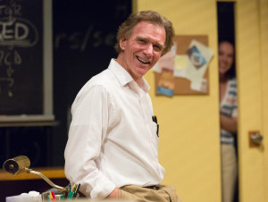 Peter DeLaurier (with Clare Mahoney in the background) in Lantern Theater Company's QED (Photo credit: Mark Garvin).
