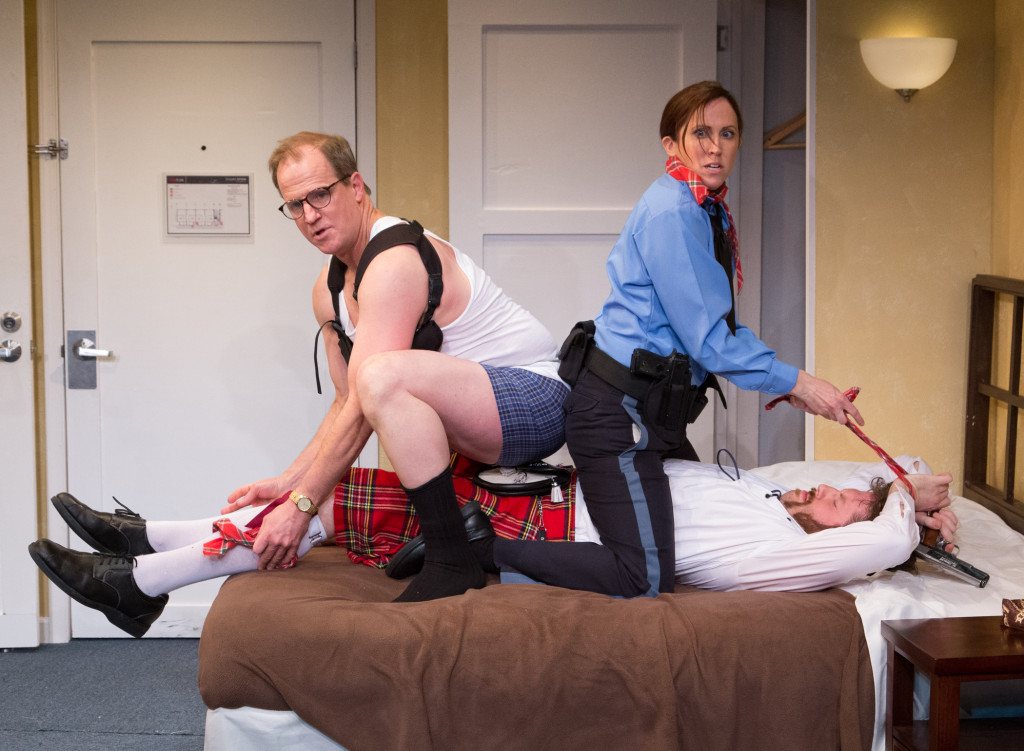 Officers Eric Sheridan (Anthony Lawton) and Billie Dwyer (Karen Peakes) tie up Todd (Jake Blouch) in Act II Playhouse's UNNECESSARY FARCE. Photo by Mark Garvin.