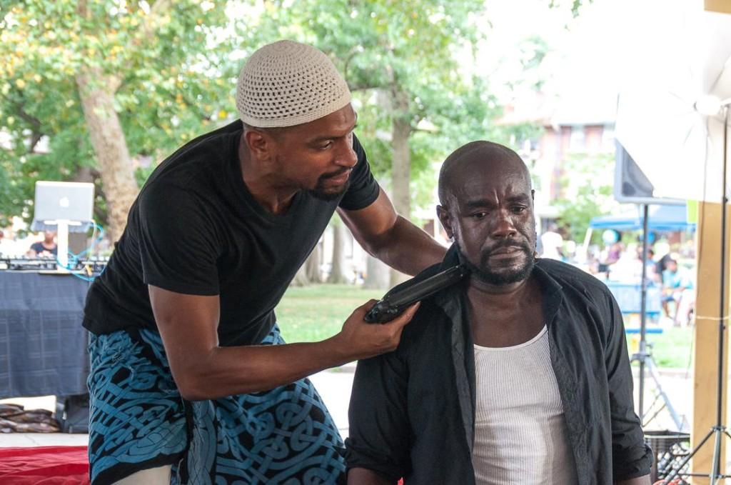Carlo Campbell as Othello draws his gun on Dwayne Thomas as Iago in Theatre in the X's OTHELLO.