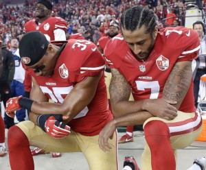 Colin Kaepernick right) and teammate kneeling during the national anthem.